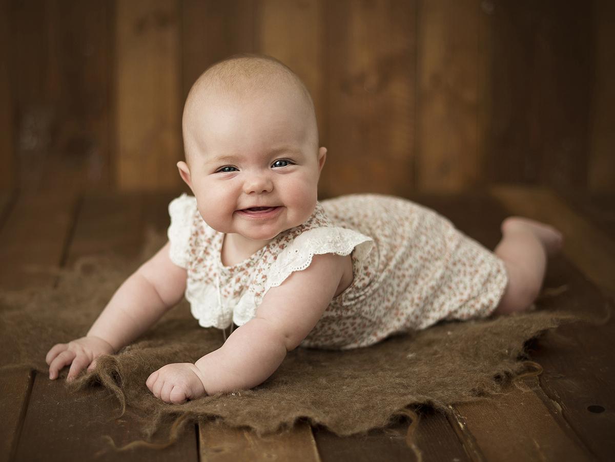 En mysig barnfotografering i ateljé med träbakgrund