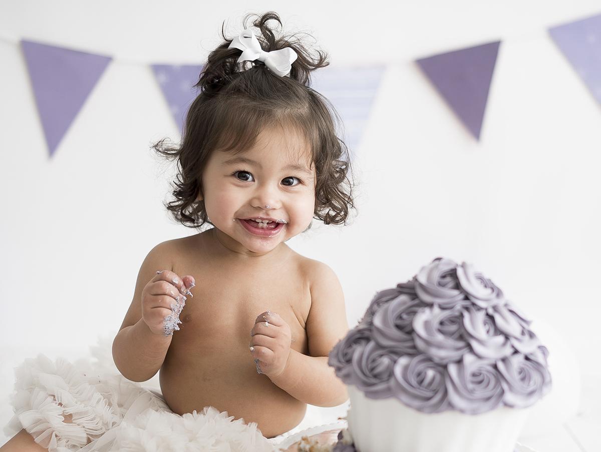 Lila cupcaketårta och glad bebis